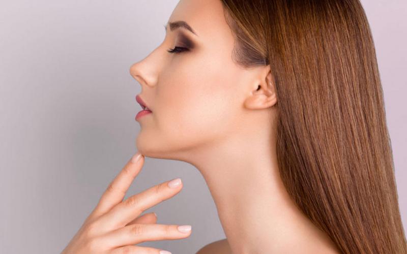 kobieta dotyka swoją szyję